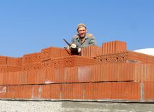 Male construction worker at a construction site brick building holding tool smiling cheerful royalty free stock photography