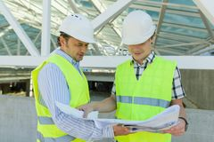 Male construction worker and engineer at the construction site. Building, development, teamwork and people concept.  royalty free stock images