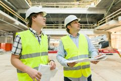 Male construction worker and engineer at the construction site. Building, development, teamwork and people concept.  royalty free stock photography