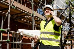 Construction worker, foreman or architect on construction site talking on his cell phone and holding rolled building plans. Male construction worker, foreman or royalty free stock photo