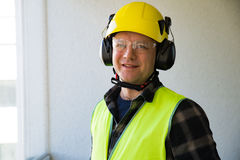 Male construction worker in hard hat drilling concrete wall Stock Photo