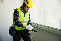 Male construction worker in hard hat drilling concrete wall Royalty Free Stock Photos