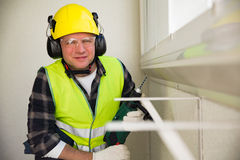 Male construction worker in hard hat drilling concrete wall Stock Photos