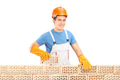 Male construction worker holding a brick behind brick wall Royalty Free Stock Photo