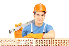 Male construction worker holding a bubble level and resting on a Royalty Free Stock Photography