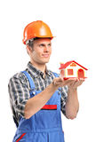 Male construction worker holding a model house. A male construction worker wearing helmet and holding a model house isolated on white background Royalty Free Stock Photo