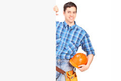 Male construction worker standing behind blank panel Royalty Free Stock Photo