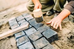 Construction worker using granite cobblestone blocks to create path or sidewalk Stock Image