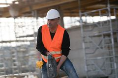 Male construction worker using jackhammer. Outdoors Stock Images