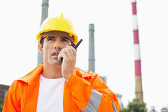 Male Construction Worker Wearing Reflective Workwear Communicating On Walkie-talkie At Site Royalty Free Stock Photos