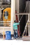 Male construction worker working on renovation of retail store. New York City, USA - June 25, 2018: Male construction worker working on renovation of retail royalty free stock photos