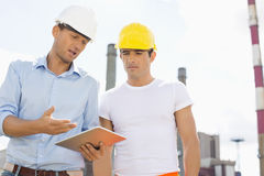Male construction workers discussing over digital tablet at industry Royalty Free Stock Photos