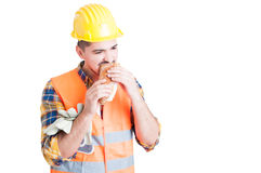 Male constructor is eating a tasty sandwich in his break Royalty Free Stock Image