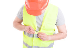 Male constructor with helmet and vest gets ready for work. As safety uniform concept isolated on white background Royalty Free Stock Image