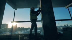 Male constructor is polishing a column at the building site