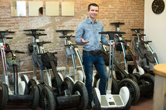 Male consultant in segways rental agency. Friendly smiling male consultant in front of segways at rental agency Royalty Free Stock Photography