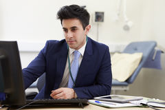 Male Consultant Working At Desk In Office Royalty Free Stock Photography