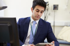 Male Consultant Working At Desk Using Digital Tablet Royalty Free Stock Image
