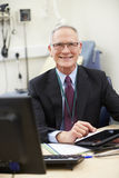 Male Consultant Working At Desk Using Digital Tablet Royalty Free Stock Photography