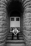 Male contemplation. A monochrome picture of a young man in cap and braces sitting on the stairs of an old brick building Royalty Free Stock Image