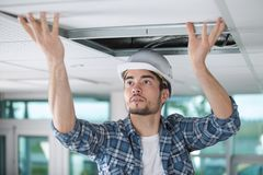 Male contractor fitting ceiling panel. Contractor stock images