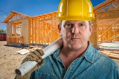 Male Contractor in Hard Hat Holding Floor Plans At Construction Site. Serious Contractor in Hard Hat Holding Floor Plans At Construction Site Royalty Free Stock Images