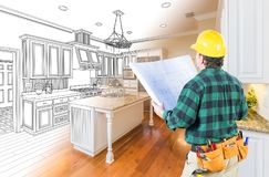 Male Contractor with Hard Hat and Plans Looking At Custom Kitchen Stock Images