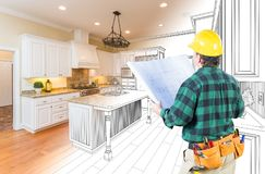 Male Contractor with Hard Hat and Plans Looking At Custom Kitchen Royalty Free Stock Image
