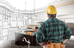 Male Contractor in Hard Hat and Tool Belt Look At Custom Kitchen. Male Contractor with acHard Hat and Tool Belt Looking At Custom Kitchen Drawing Photo stock images