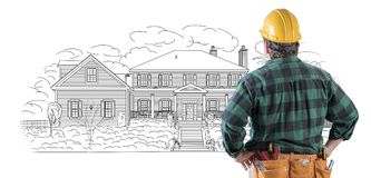 Male Contractor in Hard Hat and Tool Belt Looking At Custom Home Royalty Free Stock Image
