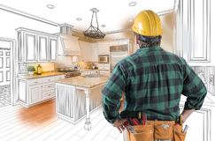Male Contractor in Hard Hat and Tool Belt Looking At Custom Kitchen Stock Photo