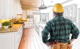 Male Contractor in Hard Hat and Tool Belt Looking At Custom Kitchen Royalty Free Stock Photos