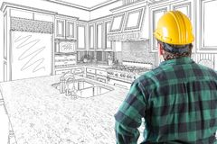 Male Contractor in Hard Hat and Tool Belt Looking At Drawn Custom Kitchen Royalty Free Stock Photography