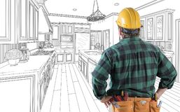 Male Contractor in Hard Hat and Tool Belt Looking At Kitchen Drawing royalty free illustration