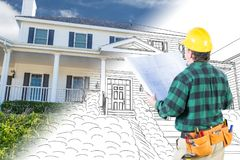 Male Contractor with Hard Hat and Tool Belt Looks At Custom Home. Male Contractor with Hard Hat and Tool Belt Looking At Custom House Drawing Photo Combination Royalty Free Stock Photo
