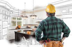 Male Contractor with Hard Hat, Tool Belt Looks at Kitchen Design. Male Contractor with Hard Hat and Tool Belt Looking At Custom Kitchen Drawing Photo Combination stock image