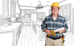 Male Contractor With House Plans Wearing Hard Hat In Front of Cu. Stom Kitchen Drawing stock photo