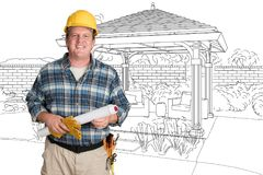 Friendly Male Contractor With House Plans Wearing Hard Hat In Front of Cu. Male Contractor With House Plans Wearing Hard Hat In Front of Custom Pergola Patio stock photo