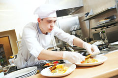 Male cook chef decorating food on the plate Royalty Free Stock Photos