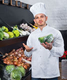 Male cook choosing vegetables in grocery shop Royalty Free Stock Photo