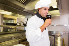 Male cook drinking red wine in kitchen Stock Photos