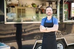 Male cook with a food truck. Portrait of a handsome young man with an apron standing in front of his food truck stock photos