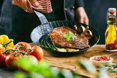 Male cook lifting up pan filled with meat royalty free stock photos