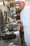 Male cook making chicken in frying pan Royalty Free Stock Images