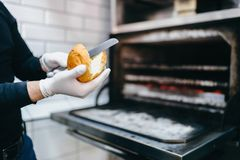 Male cook prepares bread for burger Stock Photography