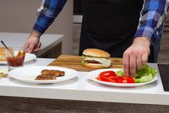 Male cook preparing cheeseburgers and hamburgers in the kitchen, on the table are the ingredients stock photos