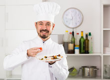 Male cook preparing food Stock Images