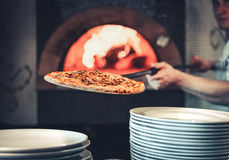 Male cook pulls out the finished pizza Royalty Free Stock Photos