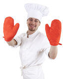 Male cook with red kitchen gloves. Male cook in white uniform and hat with red kitchen gloves, white background Stock Photo