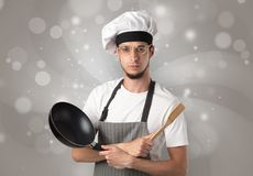 Male cook with shiny grey wallpaper. Male cook with kitchen tools and shiny grey wallpaper Royalty Free Stock Images